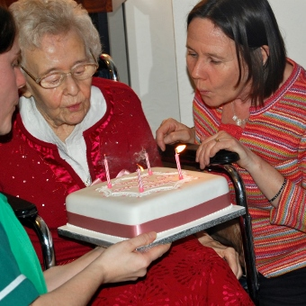 Kim blows out the candles on a birthday cake being held by her elderly mother.